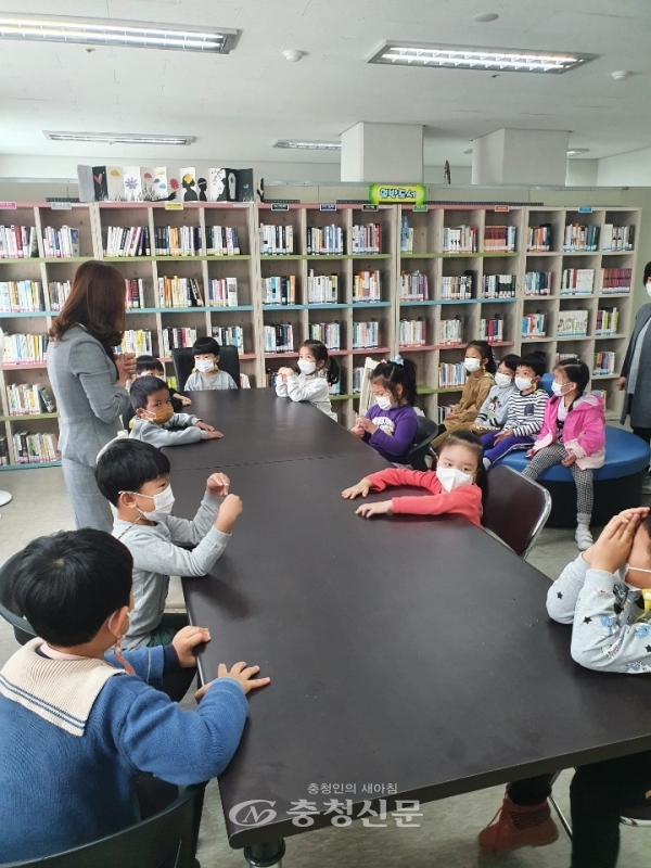 어린이들이 독서지도자로부터 책에 대한 설명과 교육을 받고 있다.
